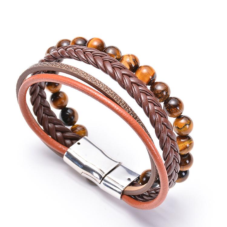 Bracelet pour homme composé de trois lanières en cuir marron tressé et lisse, et d'un anneau de perles œil de tigre.