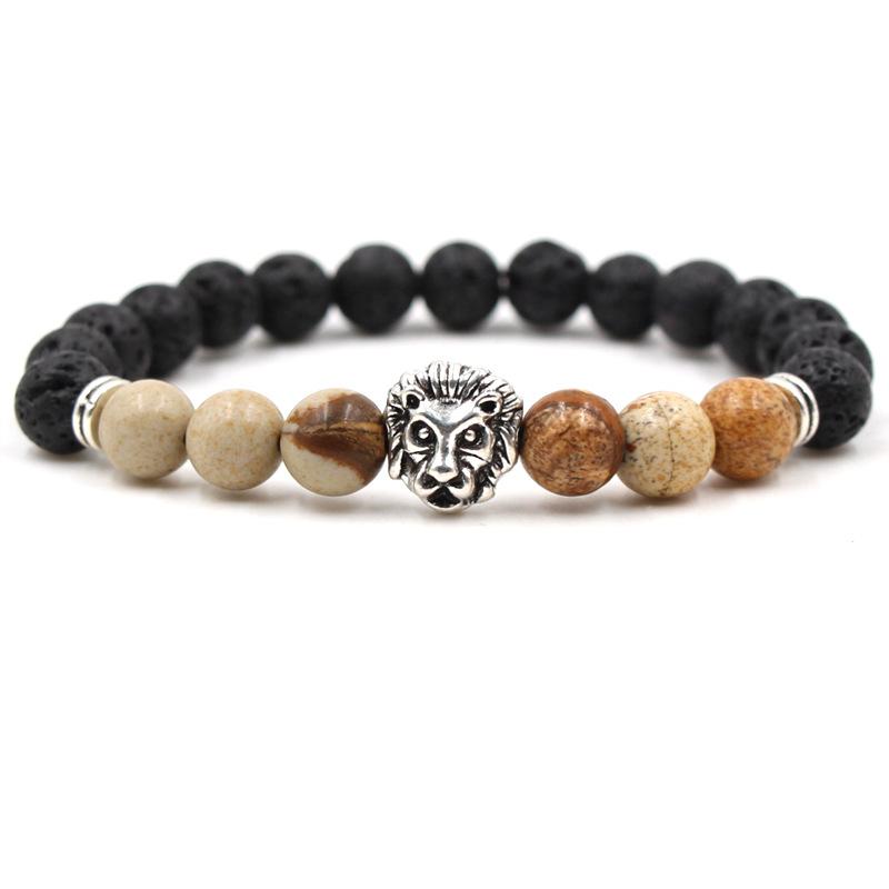 Bracelet pour homme composé d'une élégante tête de lion couleur argent, de perles de pierre de lave et de perles de jaspe scénique.