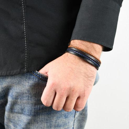 Bracelet en cuir pour homme avec deux lanières de cuir tressé bleu et marron, et deux lanières de cuir lisse noir et marron.