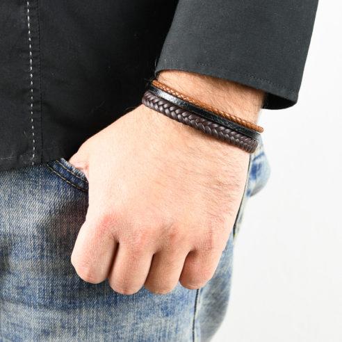 Bracelet en cuir pour homme avec deux lanières de cuir tressé marron foncé et clair, et une lanière de cuir lisse noir au centre.