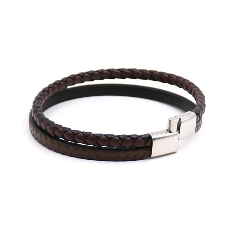 Bracelet pour homme composé d'une lanière de cuir tressé marron et noir, et d'une autre en cuir lisse marron avec d'élégants motifs.